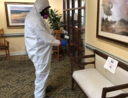Cleaner in hazmat suit performing COVID-19 disinfection